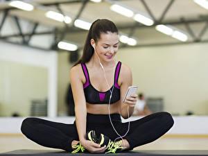 Fotos Fitness Smartphones Kopfhörer Unscharfer Hintergrund Lächeln Brünette Pose Hand Bein Sitzend junge frau