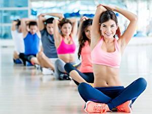 Fotos Fitness Joga Posiert Brünette Sitzend Lächeln Uniform Bauch Hand Bein junge frau Sport