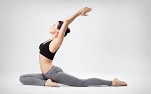 Bilder Fitness Joga Posiert Hand Bein Dehnübung Grauer Hintergrund junge frau Sport