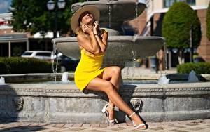 Pictures Fountains Frock Dress Yellow Hat Hands Smile Beautiful Sit Posing Young woman Girls