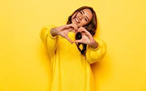Fotos Gestik Braune Haare Lächeln Glücklich Sweatshirt Gelb Hand Herz junge frau