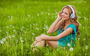 Fotos Gras Seitlich Sitzend Braunhaarige Hand Kopfhörer junge frau