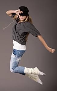 Bilder Grauer Hintergrund Baseballmütze Sprung Tanz Jeans Hand Mädchens
