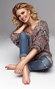 Fotos Grauer Hintergrund Blondine Lächeln Sitzend junge Frauen