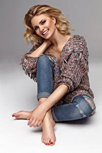 Fotos Grauer Hintergrund Blondine Lächeln Sitzend Mädchens