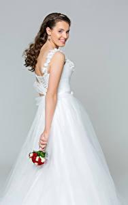 Bilder Grauer Hintergrund Braunhaarige Brautpaar Kleid Lächeln