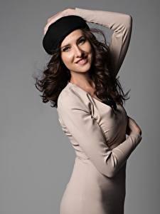 Fotos Grauer Hintergrund Braunhaarige Hand Kleid Pose Starren Lächeln Barett Mädchens