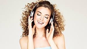 Bilder Grauer Hintergrund Braune Haare Kopfhörer Hand Lächeln Niedlich Mädchens Musik