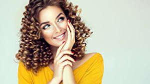Wallpaper Curly Gray background Brown haired Smile Hands Staring Glance Hairdo Young woman Girls