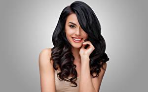 Bilder Grauer Hintergrund Brünette Haar Hand Lächeln Starren Frisur junge Frauen