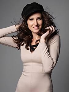 Hintergrundbilder Grauer Hintergrund Hand Kleid Starren Lächeln Braunhaarige Barett junge frau