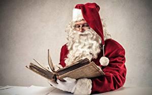 Bilder Grauer Hintergrund Weihnachtsmann Buch Mütze Brille Barthaar Sitzend