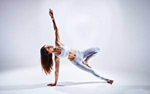 Fotos Gymnastik Grauer Hintergrund Braune Haare Joga Posiert Hand Bein junge Frauen