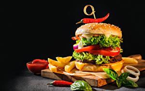 Bilder Hamburger Brötchen Fritten Chili Pfeffer Gemüse Schwarzer Hintergrund Schneidebrett
