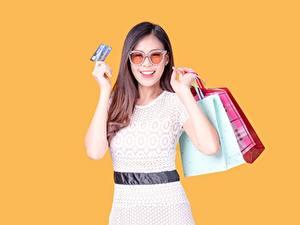 Hintergrundbilder Handtasche Einkaufen Braune Haare Brille Lächeln Hand Farbigen hintergrund Tüte junge frau