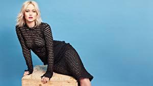 Hintergrundbilder Jennifer Lawrence Farbigen hintergrund Blond Mädchen Kleid Sitzend Hand Blick