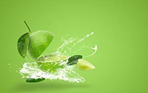 Bilder Limette Farbigen hintergrund Wasser spritzt Grün das Essen