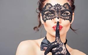 Bakgrundsbilder på skrivbordet En mask Gester Fingrar Fotomodell Ser Röda läppar Handskar Hand Grå bakgrund Ansikte ung kvinna