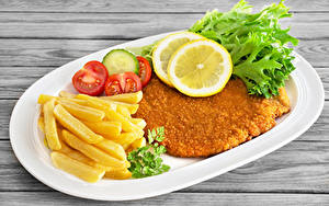Fotos Fleischwaren Pommes frites Gemüse Zitrone Fast food Teller Lebensmittel Lebensmittel