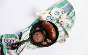 Bilder Fleischwaren Frankfurter Würstel Pilze Knoblauch Zucht-Champignon Weißer hintergrund Bratpfanne das Essen