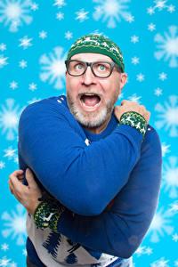 Fotos Mann Neujahr Sweatshirt Mütze Brille Hand Schneeflocken Staunen