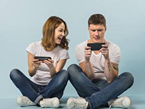 Bilder Mann Farbigen hintergrund Zwei Sitzt Smartphone Braune Haare Lacht Hand Jeans Spielt