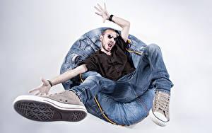 Bilder Mann Grauer Hintergrund Sessel Sitzend Jeans Hand Brille