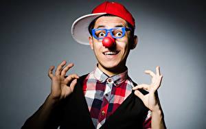 Fotos Mann Grauer Hintergrund Clowns Baseballmütze Brille Nase Hand