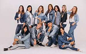 Bilder Mann Grauer Hintergrund Lächeln Blick Jeans Jacke Mädchens
