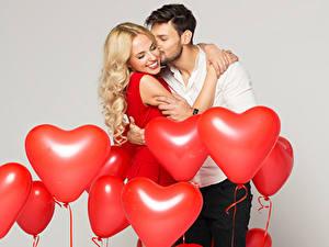 Fotos Mann Liebe Paare in der Liebe Grauer Hintergrund Luftballons Herz Blondine Umarmen Lächeln Küsst 2 junge frau