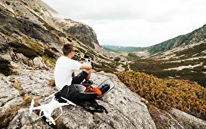 Bilder Mann Gebirge Quadrocopter Felsen Sitzend Rucksack Natur
