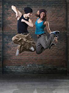 Fotos Mann Mauer 2 Tanzen Sprung Glücklich Hand Mütze Mädchens
