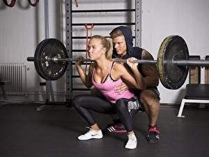 Bilder Mann Trainieren 2 Blondine Sitzend Hantelstange Bein Kniebeugen sportliches Mädchens