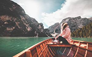 Hintergrundbilder Berg See Italien Boot Jacke Sitzt Lake Braies junge frau Natur