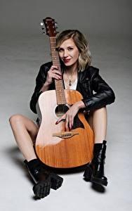 Bilder Musikinstrumente Grauer Hintergrund Blondine Gitarre Jacke Sitzt Bein Mädchens