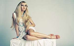 Fotos Halskette Grauer Hintergrund Blond Mädchen Kleid Sitzt Hand Posiert Bein Mädchens