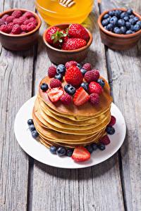 Fotos Eierkuchen Erdbeeren Himbeeren Heidelbeeren Bretter Teller Lebensmittel