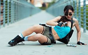 Fotos Pistole Brünette Hinlegen Hand Brille Handschuh Shorts Bein Boots Cosplay Lara Croft junge frau