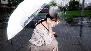 Bilder Regen Asiatische Sitzen Regenschirm Braune Haare Unscharfer Hintergrund Mädchens