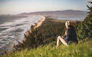 Bilder Meer Küste Gras Mütze Sitzen Mädchens