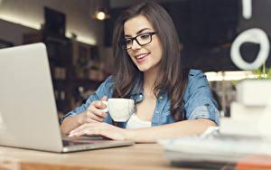 Fotos Sitzend Notebook Brille Lächeln Hand Becher Bokeh Brünette Mädchens
