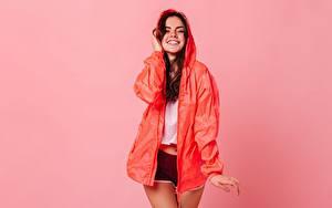 Bilder Lächeln Pose Shorts Umhang Farbigen hintergrund junge frau