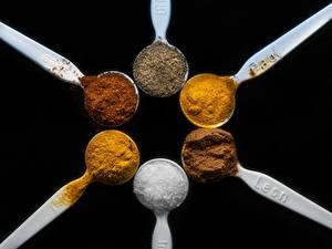 Fotos Gewürze Großansicht Schwarzer Hintergrund Löffel Salz cinnamon, saffron Kurkuma, Cayenne papper Lebensmittel