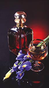 Fotos Stillleben Schwertlilien Whiskey Schwarzer Hintergrund Flasche Weinglas Lebensmittel