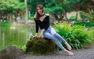Fotos Stein Asiaten Laubmoose Strauch Braune Haare Sitzen Hand Bein Jeans Stöckelschuh junge frau