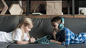 Desktop hintergrundbilder Tablet-PC Junge Kleine Mädchen 2 Kopfhörer Hinlegen Sofa kind