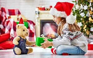 Bilder Teddybär Neujahr Geschenke Kleine Mädchen Lächeln Mütze Sitzend Sweatshirt Kinder
