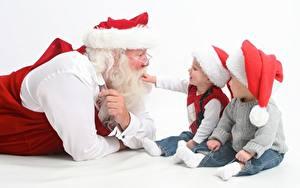 Fotos Drei 3 Weißer hintergrund Sitzt Junge Sweatshirt Weihnachtsmann Mütze Brille Barthaar Kinder