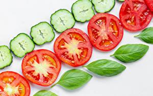 Bilder Tomaten Gurke Weißer hintergrund Geschnitten Basilikum das Essen