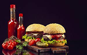 Bilder Tomate Burger Gurke Brötchen Schwarzer Hintergrund Flaschen Ketchup Schneidebrett
